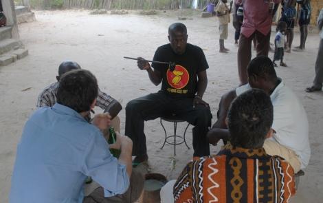 Fone (de frente) compartiendo vino de palma con miembros del equipo y otros participantes en el documental